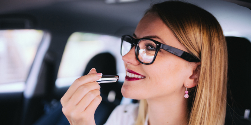 A Smiling Woman Wearing Glasses Inside The Car with Lipstick.